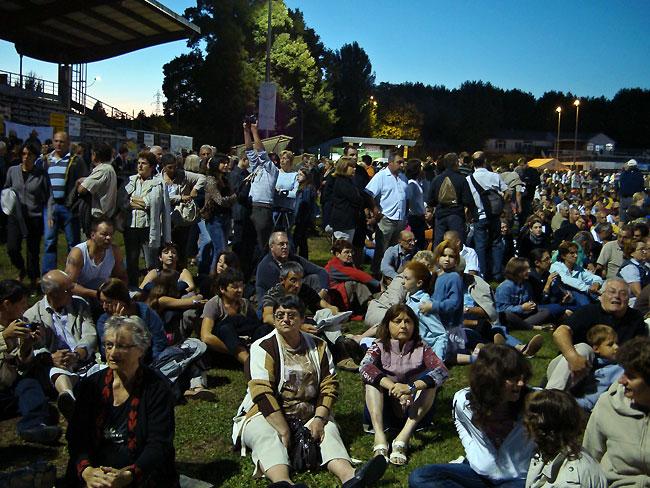 La foule attend assise sur l'herbe
